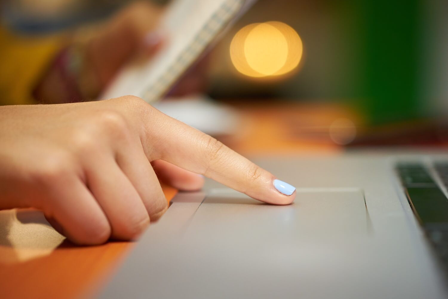 Close-up of a woman's finger on a scrolling on a laptop trackpad.