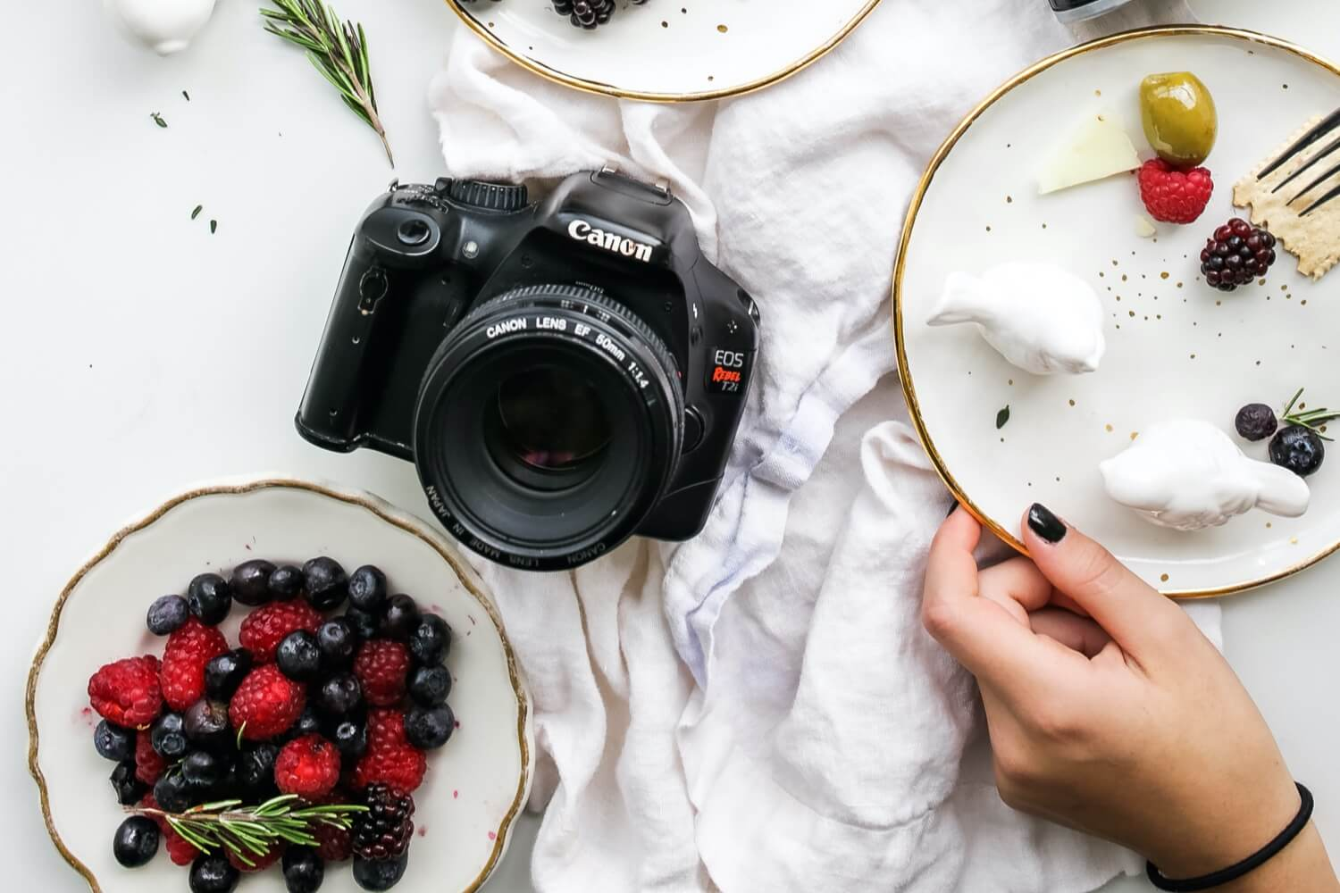 A woman eating dessert with an SLR camera on the table.