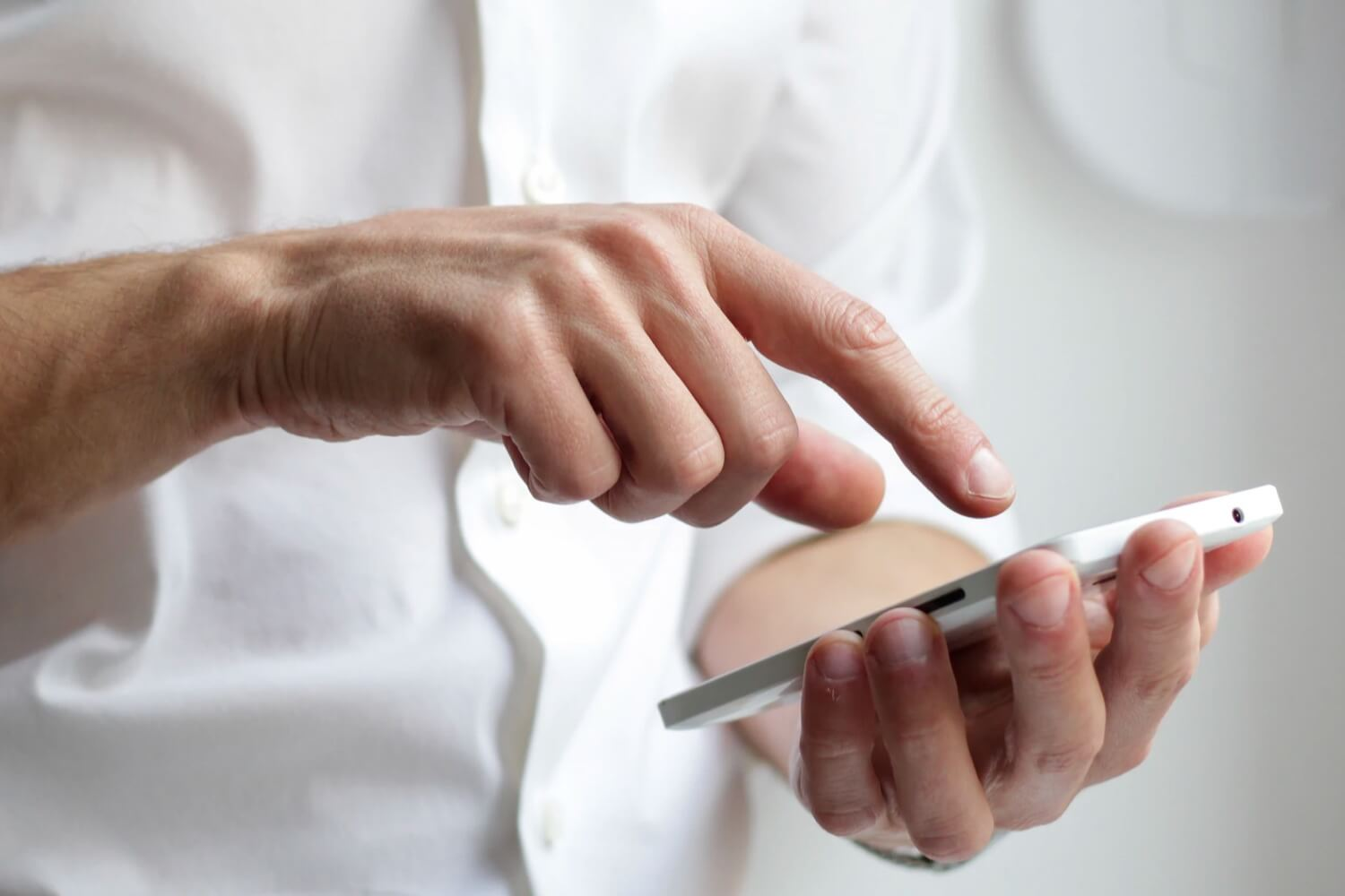 A man pointing his finger at a call to action button on his phone.