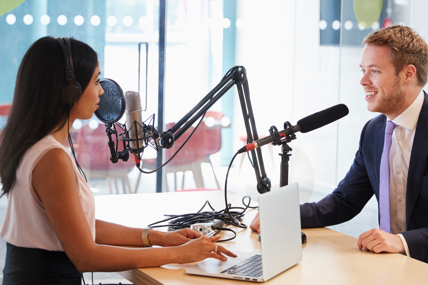 A woman interviewing a man sitting across from her in a podcast studio.