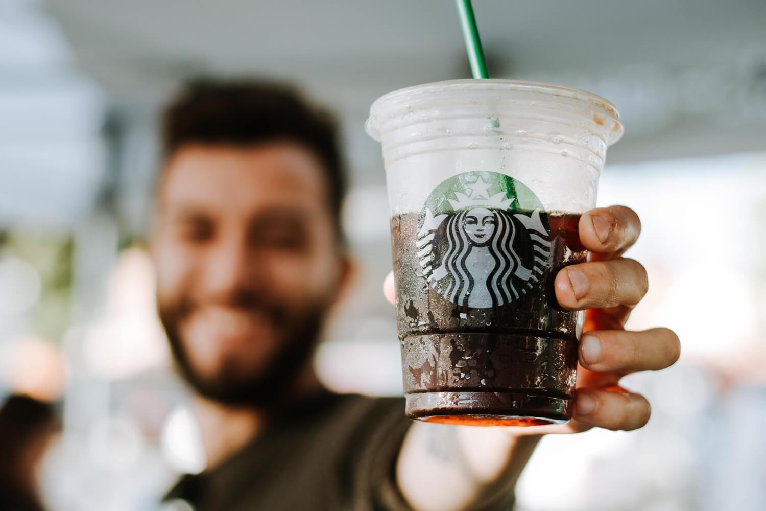 A man holding up a plastic cup of free Starbucks coffee.