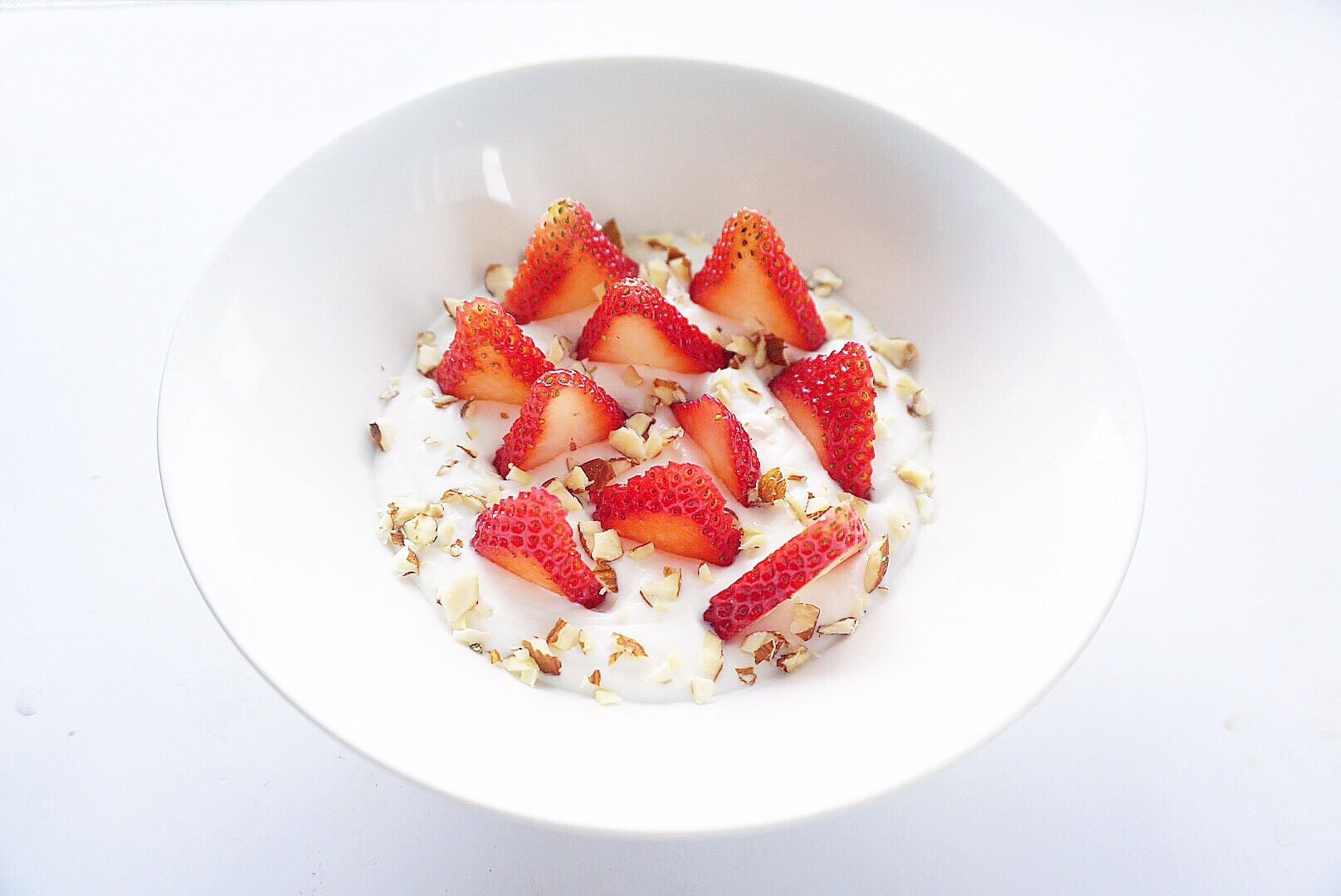 White bowl with strawberries and coconut inside