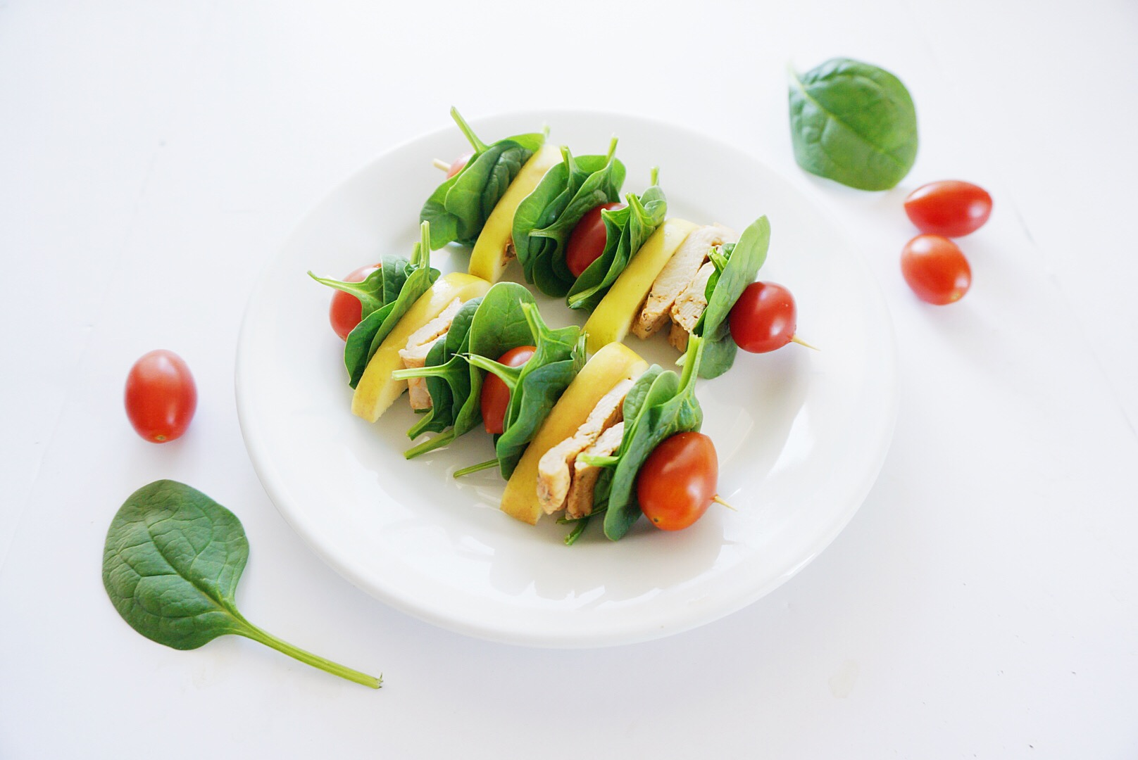 Skewers on a white plate with chicken and salad on them