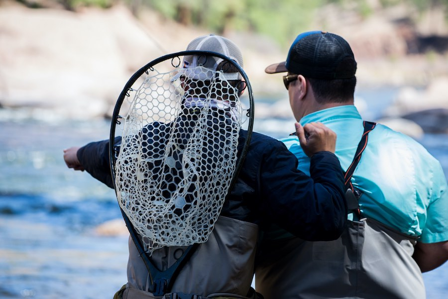 A fly fishing guide and his client reading the water.