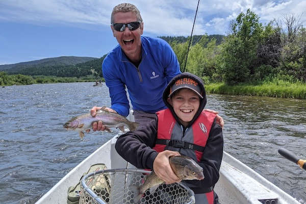 Anglers holding trout on the Madison River.