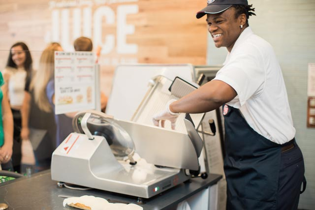 Smiling Jersey Mike's employee preparing customers food