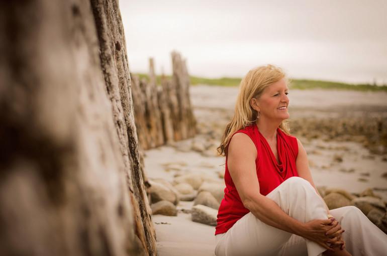 Dr. Wendy Nickerson sitting on a beach