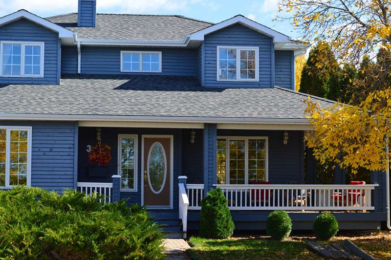 Blue siding house with white frame vinyl windows and black color dimensional asphalt shingles.