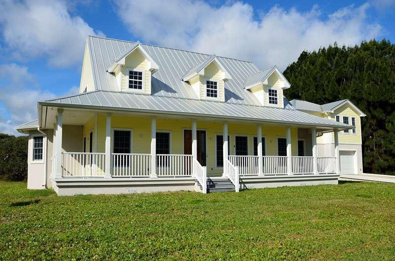 Yellow siding house with mechanical standing seam metal roof.
