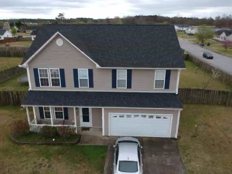 Drone picture of two story house. house have tan vinyl siding and new black color roof.