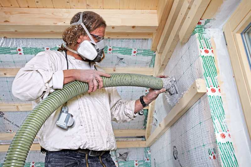 Construction worker wear safety mask and install insulation into a wall.