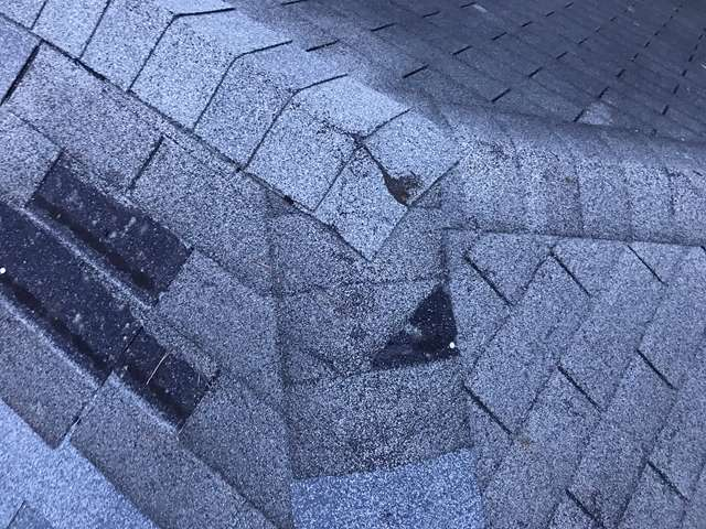 Old asphalt roof with buckling and missing shingles.