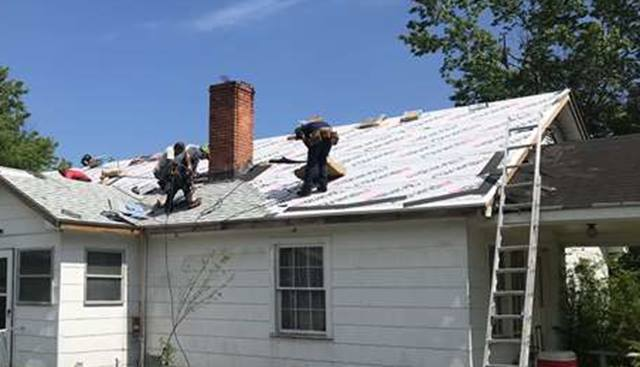 Roofers installing new roof using synthetic roofing paper.