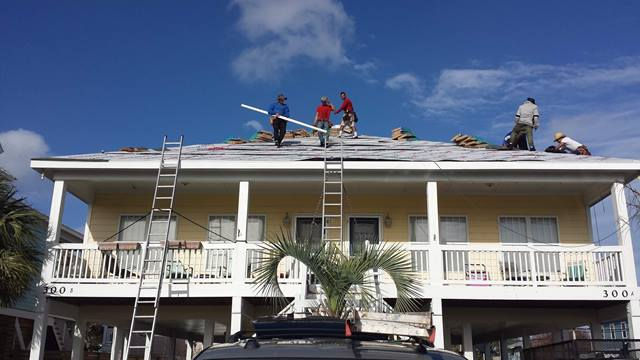 Roofers re-roofing 2 story house.