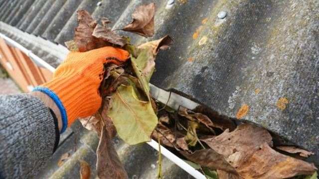 Worker clean clogged gutters from leaves.