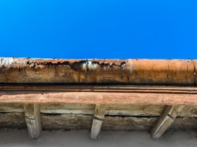 Broken and corroded galvanized metal rain gutter.
