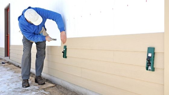 Worker installing Fiber Cement siding on a residential home.