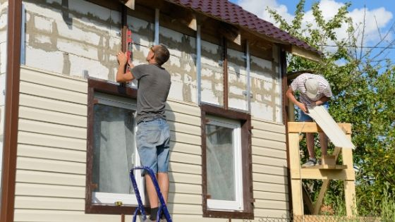 Workers installing Vinyl Siding on a residential home.