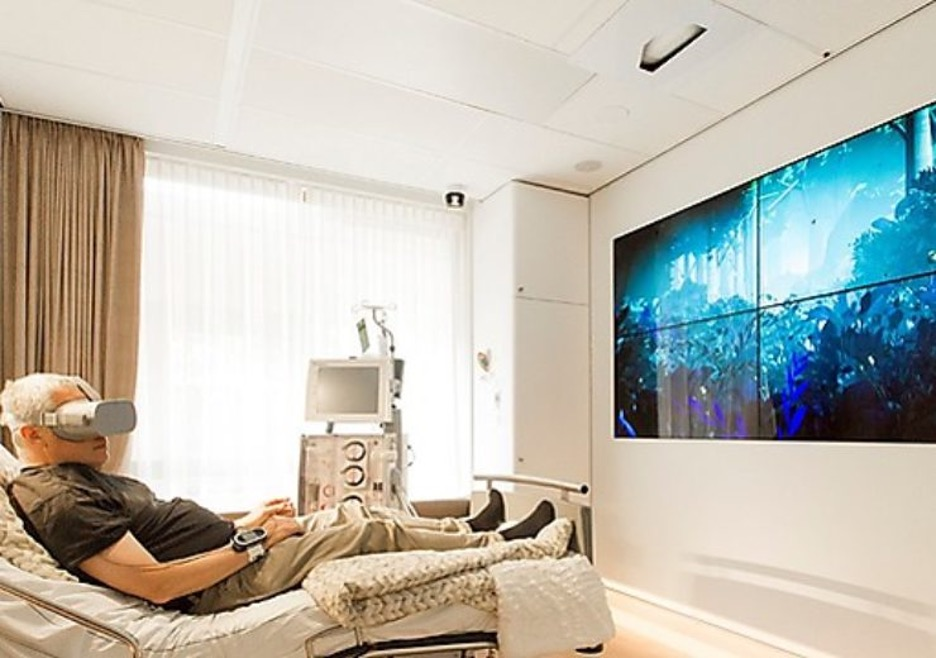 New patient room with a video wall on screen, displaying a calming nature scenery. Patient is wearing a VR headset. Ouva sensor in ther corner is watching over the room.