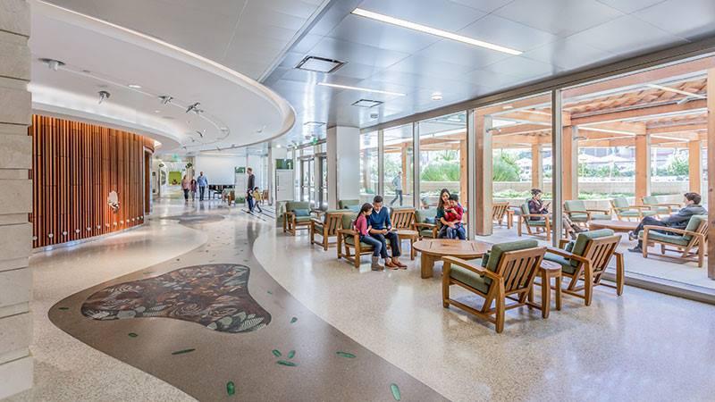Photo of a hospital lobby with seats along windows.