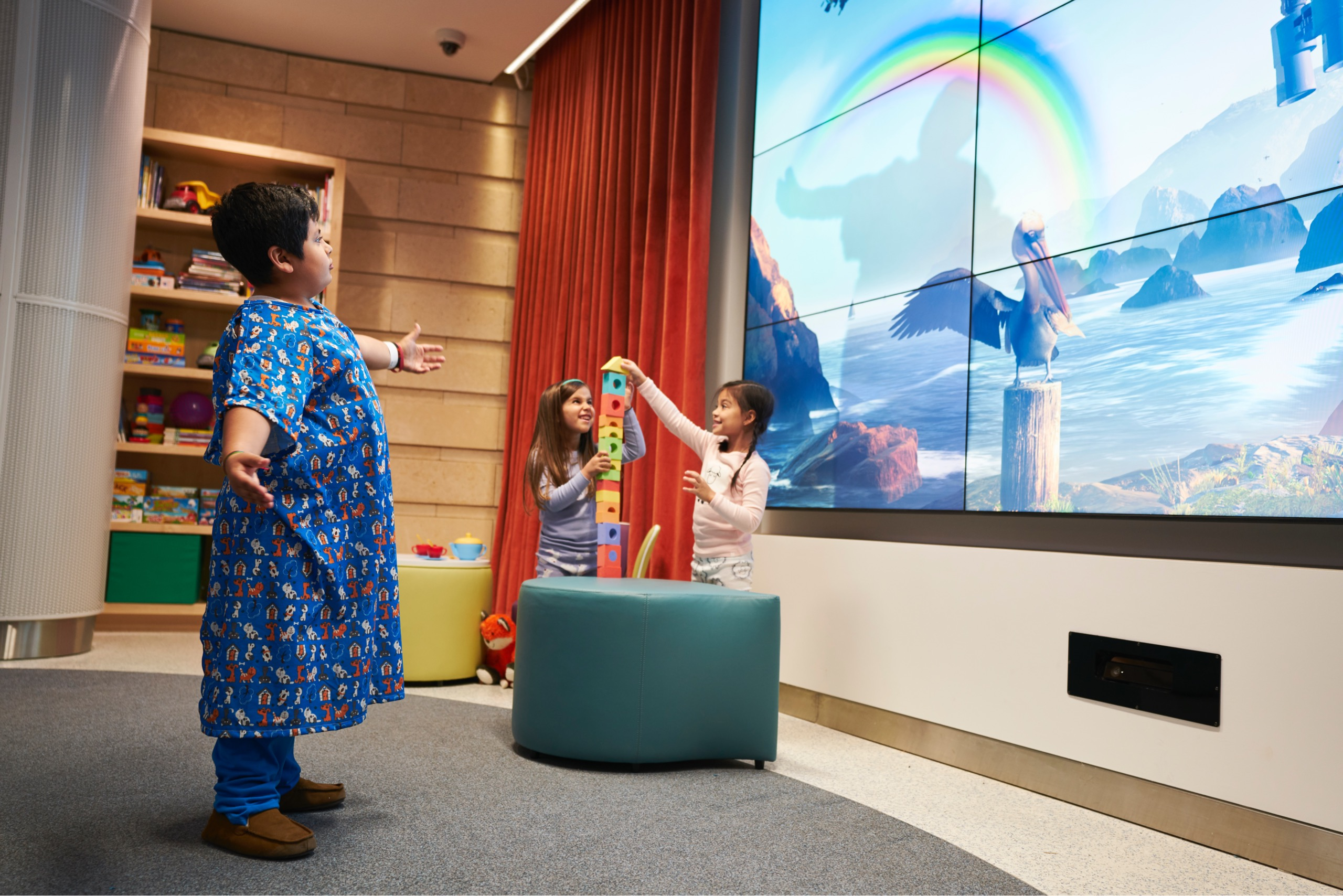A kid in robe playing with rainbow on interactive video wall at Lucile Packard Children's Hospital at Stanford