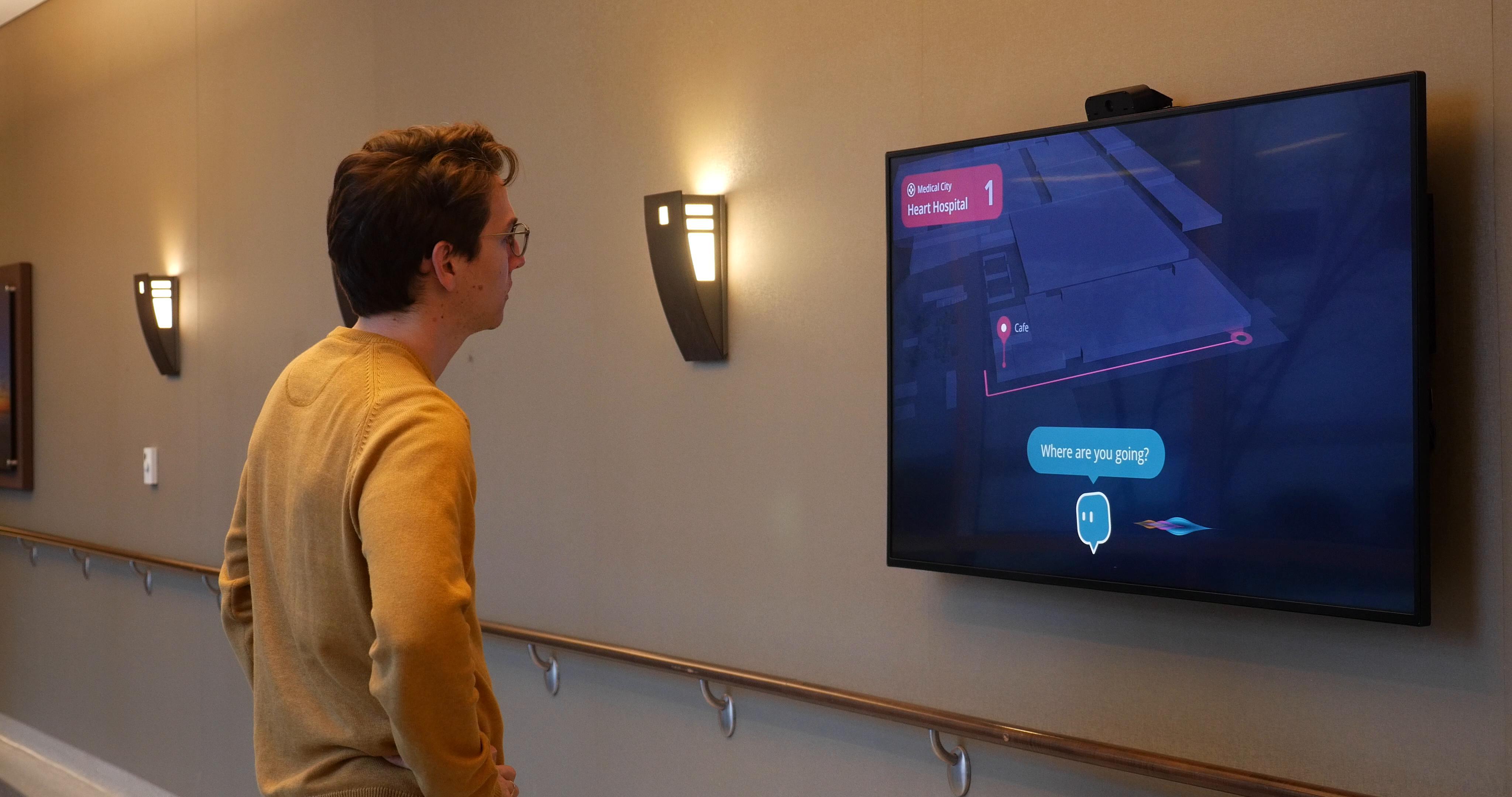 Visitor looking at interactive screen showing wayfinding directions at Medical City Heart Hospital.