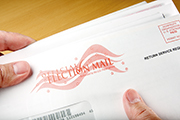 Hands holding official election mail