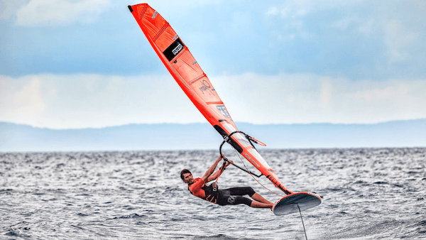 Kitesurfer dressed in an orange wetsuit gliding over the water