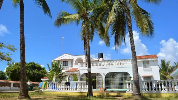 Tulia House hostel just outside of Mombasa town in the sunlight with several palm trees
