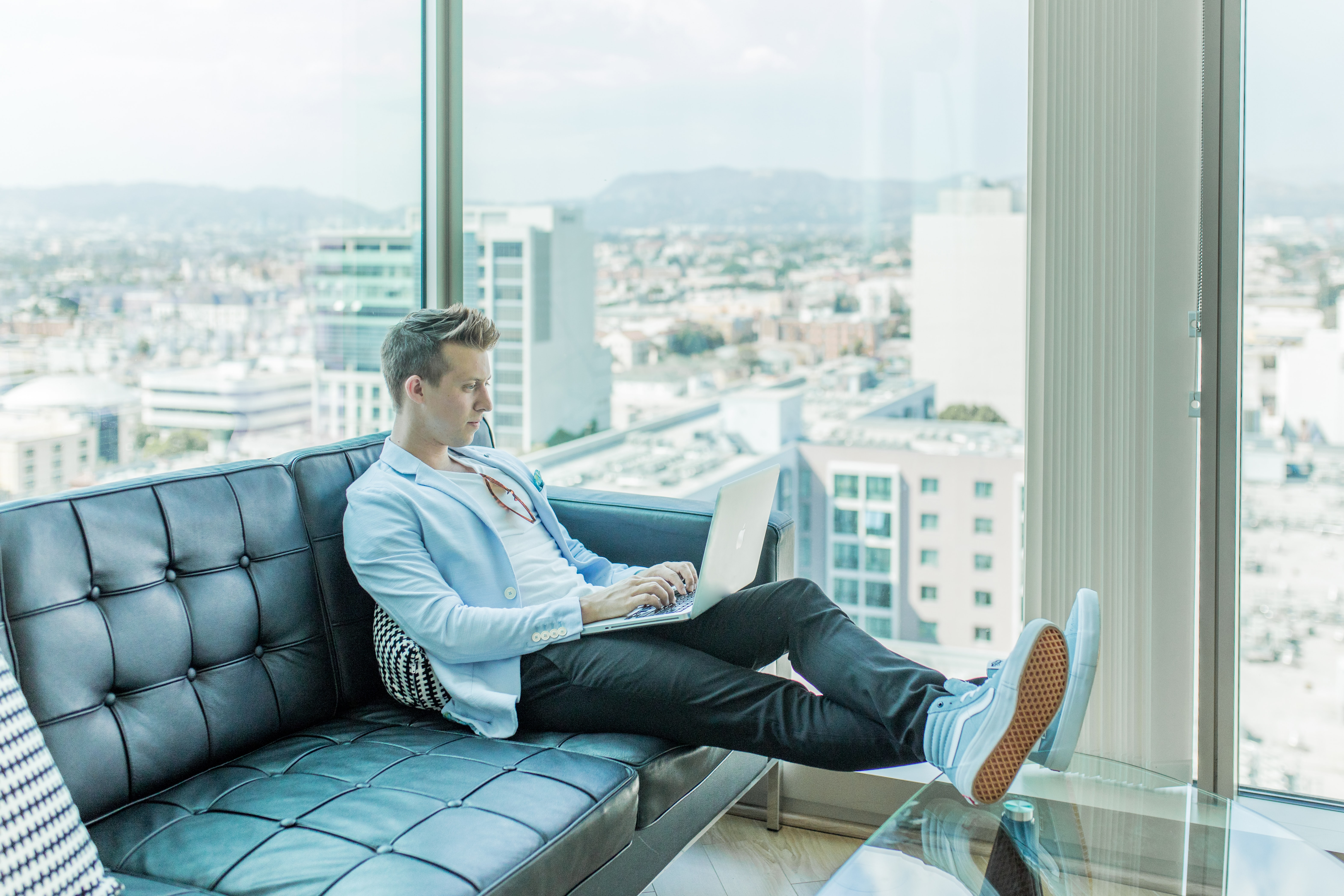 Man sitting on a sofa, working by the window