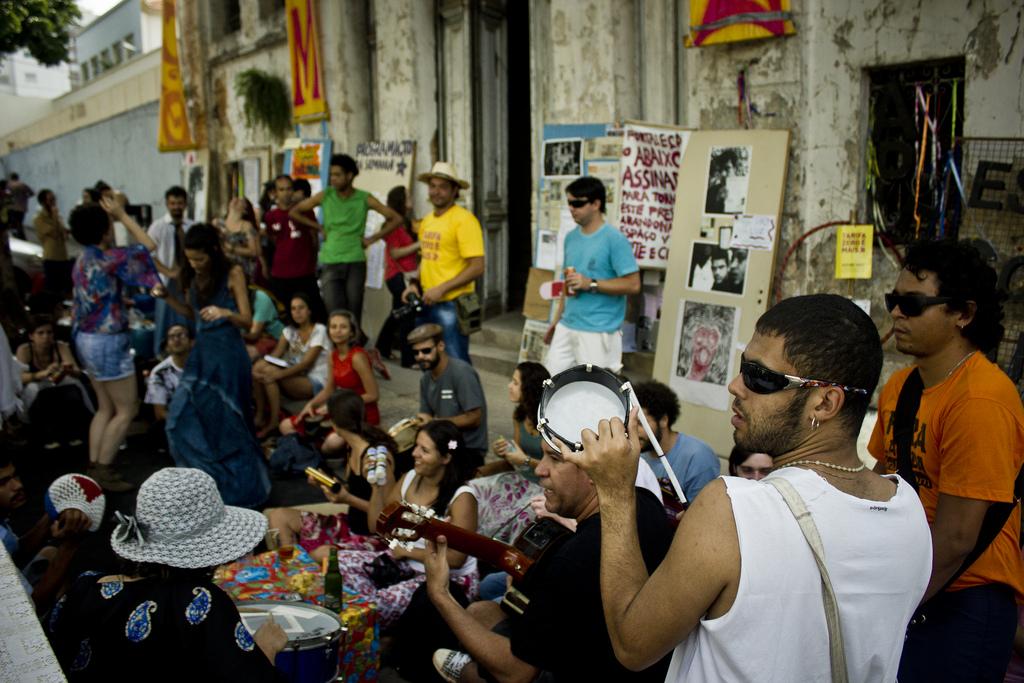 Grupo de pessoas sentadas na calçada enquanto toca instrumentos.