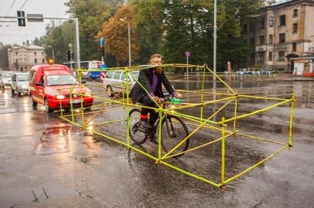 Foto de um homem andando de bicleta com uma estrutura de bambu que simula um carro para mostrar que a bicicleta ocupa menos espaço que um veículo nas ruas.