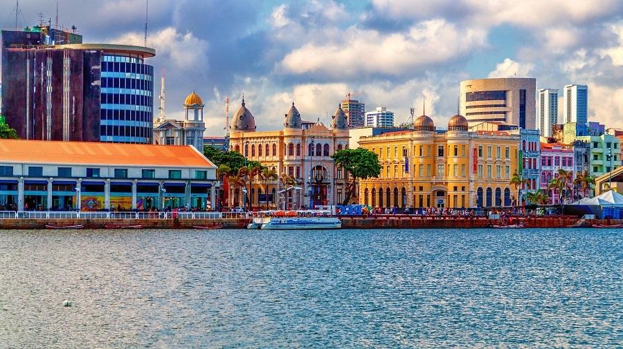 Foto da cidade de Recife com prédios históricos e o mar.