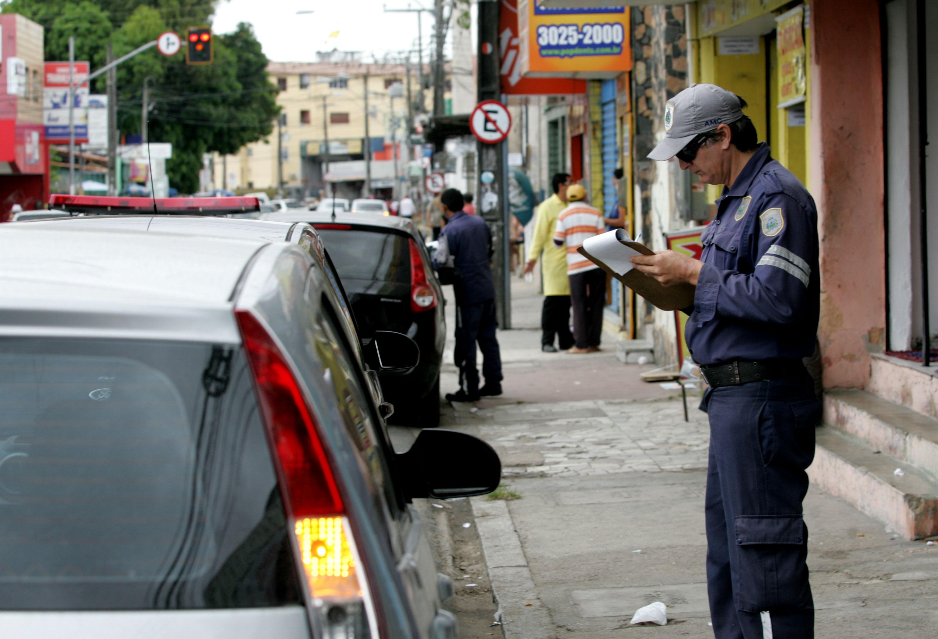 Funcionário deixando multa em carro estacionado