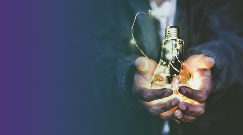 Mãos de uma pessoa segurando uma lâmpada acessa.