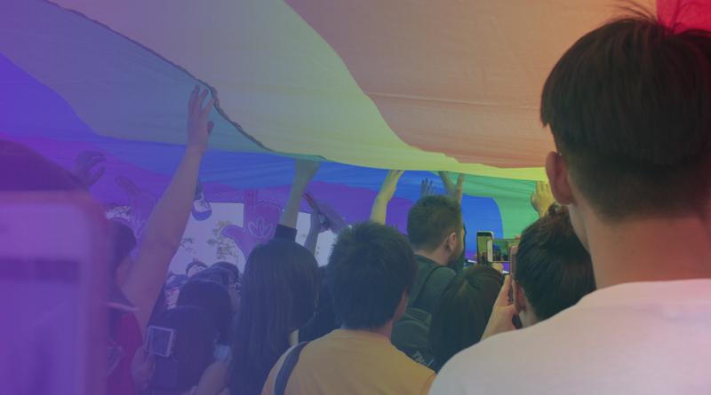 Pessoas carregam bandeira com as cores do arco-íris em protesto.
