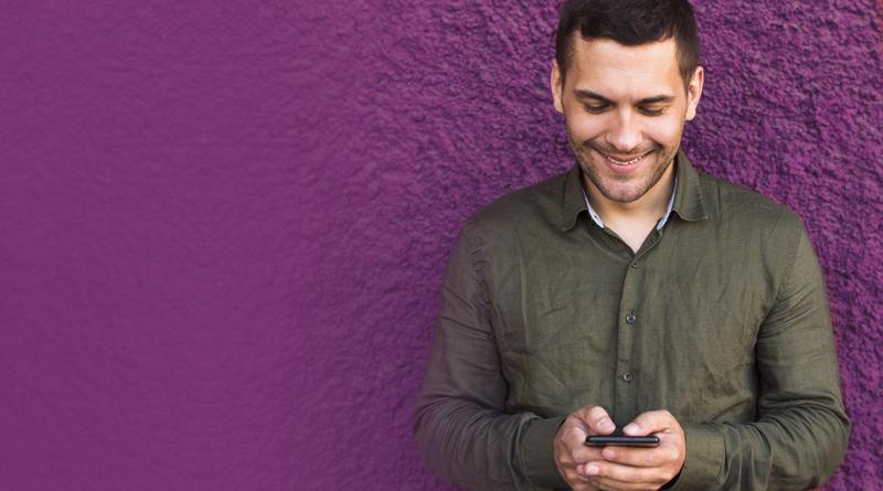 Homem olhando o celular e sorrindo