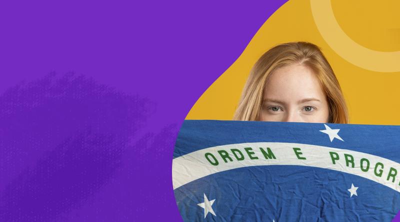 """Lado esquerdo roxo, cortando o meio da imagem. No lado direito há uma garota ruiva segurando a bandeira do Brasil em frente ao seu rosto, mostrando bem a frase """"Ordem e Progresso""""."""