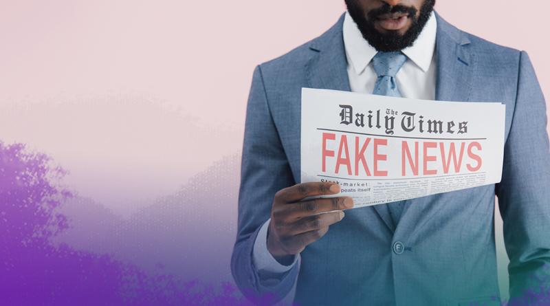 Homem de terno lê um jornal no qual está escrito Fake News