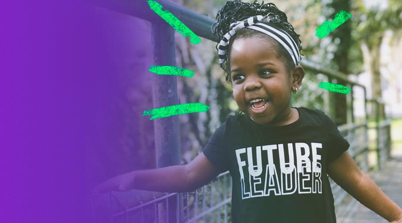 """Menina vestida com uma camiseta na qual está escrita """"Future Leader"""" sorri em uma passarela"""