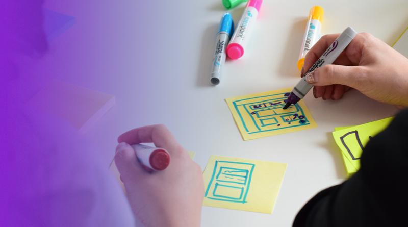 Pessoas desenham pequenos sistemas coloridos em uma folha de papel.