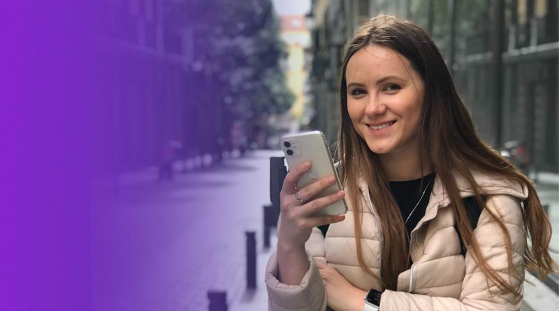 Mulher segurando um celular olha para câmera e sorri