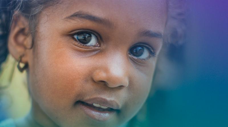 A foto mostra uma criança olhando para a câmera.