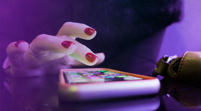 A imagem mostra uma mão feminina utilizando um smartphone disposto sobre uma mesa.