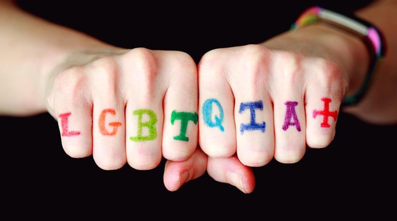 A imagem mostra duas mãos fechadas em punho, nas quais está escrito LGBTQIA+