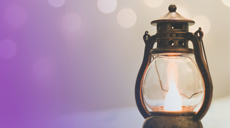 A imagem mostra uma pequena lamparina de metal acesa.