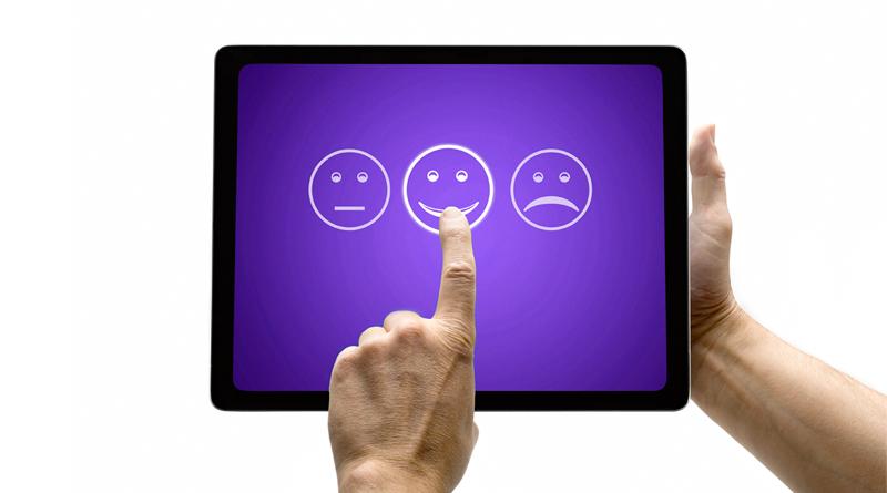 A imagem mostra duas mãos segurando um tablet preto. Na tela é possível ver um fundo roxo e três emojis brancos, com as expressões indiferente, feliz e triste, da esquerda para direita. Uma das mãos faz menção de selecionar o emoji feliz.