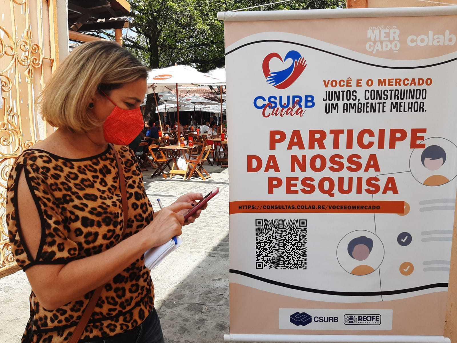 Mulher ao lado de um banner convidando que as pessoas participem da consulta.