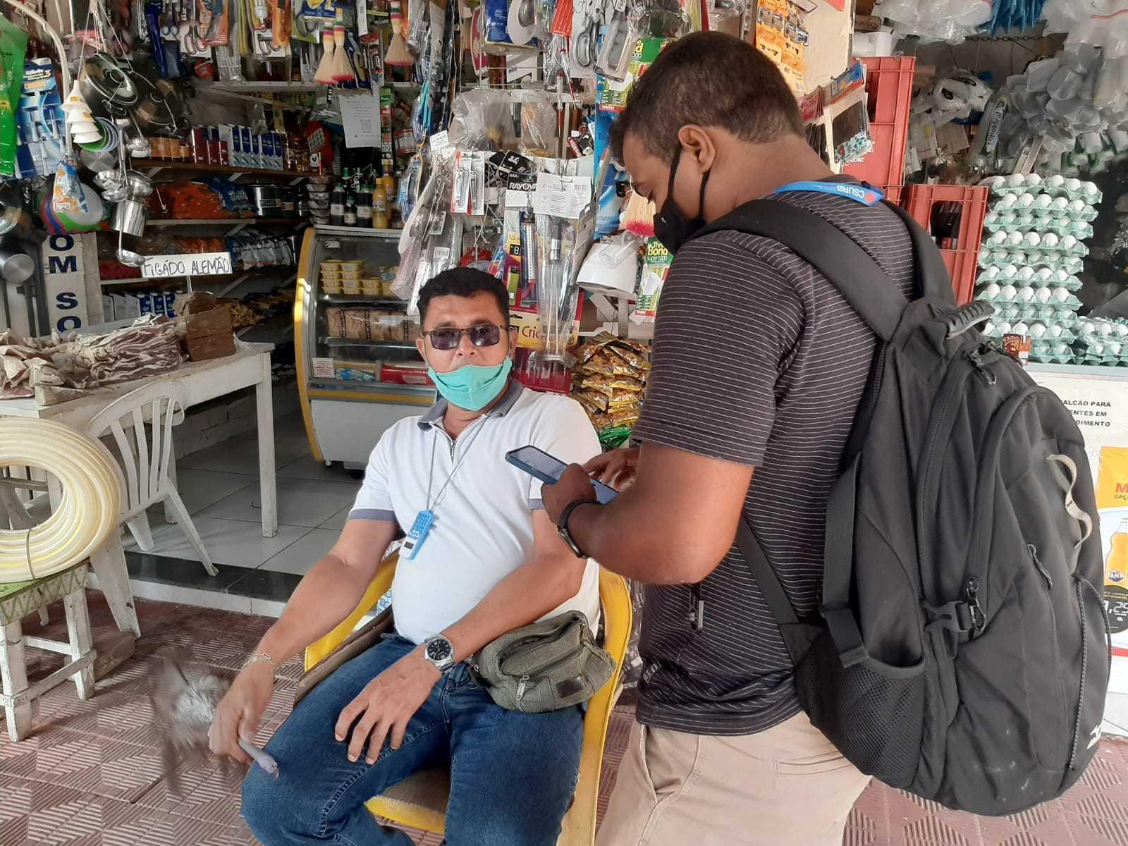 Dois homens, um em pé realizando a consulta e outro sentado, na frente de uma loja de artigos diversos.