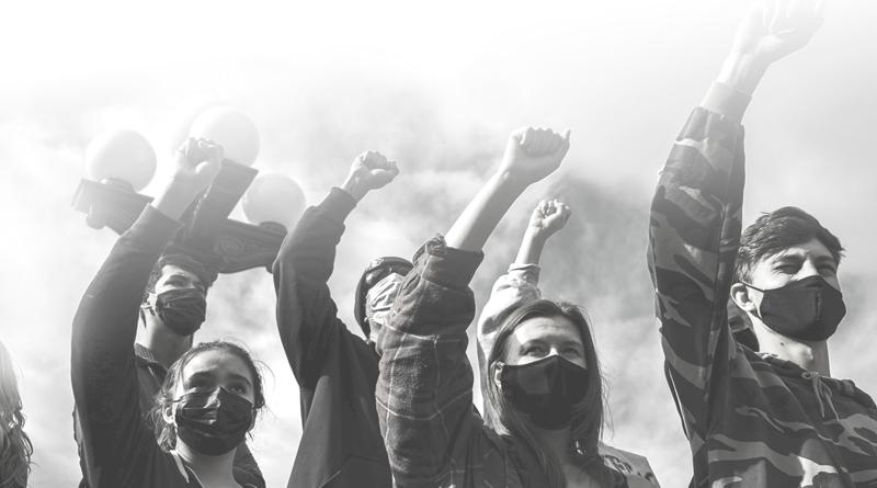 A foto em preto e branco mostra pessoas protestando com o punho erguido, em sinal de resistência e reinvindicação.